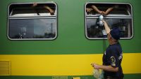 epaselect epa04911405 Water is distributed to migrants through the window of a train at Bicske Railway Station, in Bicske, 35 kms west of Budapest, Hungary, 03 September 2015. The migrants were removed from the train by police in Bicske, 35 kms west of