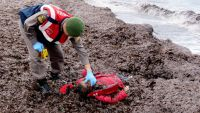 epa05088753 A Turkish soldier inspects the washed up body of a refugee who drowned during a failed attempt to sail to the Greek island of Lesvos at the shore in the coastal town Ayvalik, in Balikesir, Turkey, 05 January 2016. Media reports said at least
