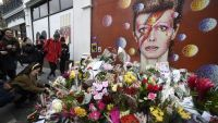 epa05098508 Bowie fans continue to bring flowers at a tribute mural for late British singer David Bowie in his birthplace Brixton, London, Britain, 12 January 2016. Well-wishers have flocked to the Bowie mural to pay their respects following the