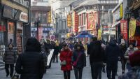 epa05110265 Citizens walk past commercial establishments at the shopping area of Qianmen district in Beijing, China, 19 January 2016. China's economy grew 6.9 percent in 2015, according to official figures released 19 January, marking the slowest