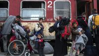 epa05178293 Refugees and migrants wait as they try to find a place on an already full train headed for Serbia, near the city of Gevgelija, The Former Yugoslav Republic of Macedonia, on 24 February 2016. Refugees and migrants from Iraq and Syria continue