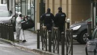 epa05230236 Police officers stand guard as an investigator walks by outside a building where an anti-terrorism operation took place in Argenteuil, near Paris, 25 March 2016. A terrorist attack had been thwarted in Paris with the arrest of a suspected
