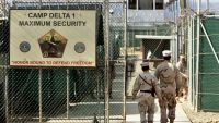 FILE - In this June 27, 2006 file photo, reviewed by a U.S. Department of Defense official, U.S. military guards walk within Camp Delta military-run prison, at the Guantanamo Bay U.S. Naval Base, Cuba. The Supreme Court is allowing the Obama