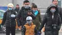 epa04560542 People wear masks walking in the street while the PM2.5 Air Quality Index (AQI) reaches more than 500 in Beijing city, China, 15 January 2015. Beijing vows to inprove the air quality and control the air pollution by 2022 as it bids for the