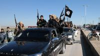 In this photo released on May 4, 2015, by a militant website, which has been verified and is consistent with other AP reporting, Islamic State militants pass by a convoy in Tel Abyad town, northeast Syria. In contrast to the failures of the Iraqi army, in