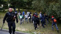 epa04867018 Migrants escape from the French Police as they try to catch a train to reach England, in Calais, France, 30 July 2015. A Sudanese man, between 25 and 30 years old, was crushed under a truck as up to 1,500 migrants tried to force their way into