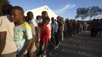 People stand in line to vote during parliamentary elections in Port-au-Prince, Haiti, Sunday, Aug. 9, 2015. Haitians are electing legislators to Parliament after a very long wait. It's been roughly eight months since the legislature was dissolved and