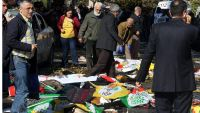 epa04971560 People cover victims with flags and banners after multiple explosions ahead of a rally in Ankara, Turkey 10 October 2015. Twin bomb blasts on 10 October killed at least 30 people outside a train station in the Turkish capital, Ankara, as pro