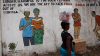 epa04911628 A Liberian woman passes a mural carrying mesages about the deadly Ebola virus on a street corner in Monrovia, Liberia, 03 September 2015. The World Health Organization (WHO) declared Liberia Ebola-free for the second time within a year.  EPA