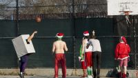 epa05066486 A man dressed as a gift (L) shoots a basketball as people in Santa Claus costumes  gather for the start of Santa Con in Brooklyn, New York, USA, on 12 December 2015. The annual event, which is held in many cities around the world, is a day