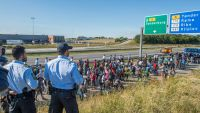 epa04922480 Policemen watch as migrants, mainly from Syria and Iraq, walk at the E45 freeway near Kliplev, Denmark, 09 September 2015. Thousands of the migrants arrived early morning at Padborg with a train from Germany and were placed at a school from