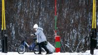 epa05028585 A refugee pushes a bike while pulking a large suitcase as she crosses the border between Norway and Russia in Storskog near Kirkenes in Northern Norway, 16 November, 2015. According to reports, for those trying to flee the conflicts in the