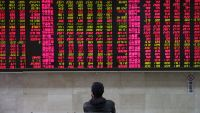 epa05027714 A stock investor watches stock prices in front of an electronic screen showing the stock prices at a brokerage house in Beijing, China, 16 November 2015. Stocks across Asia were down Monday in the first day of trading after the Paris terrorist