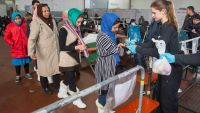 epa05088321 Newly arrived refugees line up for food on the grounds of a clearing station operated by the German federal police in the Paul Halls in Passau, Germany, 05 January 2016. More than 1 million people, mainly from war-torn countries in the Middle