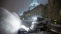 epa05119496 Workers clear snow from the East Front of the U.S. Capitol during a major blizzard in Washington, DC, USA, 22 January 2016. Winter Storm Jonas is expected to dump more than two feet (61 centimeters) of snow in the Washington, DC region