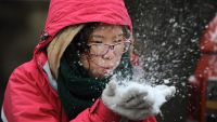 epa05121928 A tourist plays with the snow at Sapa, a mountainous town in northern Vietnam, Lao Cai province, Vietnam, 24 January 2016. Northern provinces in Vietnam has entered the coldest time of the year, according to media reports. The lowest