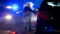 A Oregon State police officer stands by a vehicle as police officers block Highway 395 in Seneca, Ore., Tuesday, Jan. 26, 2016. Authorities said shots were fired Tuesday during the arrest of members of an armed group that has occupied a national wildlife