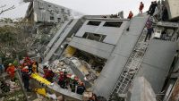 epa05145443 Rescuers search for survivors from a collapsed building following a 6.4 magnitude earthquake that struck the area in Tainan City, Taiwan, 06 February 2016. At least three people, including an infant, were killed and dozens injured when a high