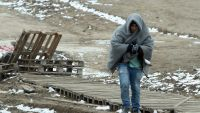 epa05123063 A boy tries to warm up in a blanket while walking in cold weather from the border between Serbia and Macedonia to a temporary camp for migrants in the village of Miratovac, on the border between Serbia and Macedonia, close to the south Serbian
