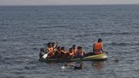 epa04889888 A Pakistani refugee swims towards a beach as others are seen on a dinghy whose engine broke down near the shore of the Greek island of Kos after crossing the sea borders with Turkey, Greece, 20 August 2015. The Greek island is struggling with