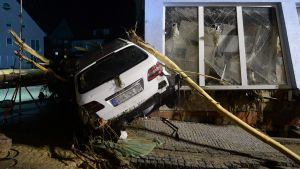epa05336908 A car sits after being transported up to the wall in front of a house by floodwater in Braunsbach, Germany, 30 May 2016. Pouring rain caused two small streams burst their banks, in the resulting flood several houses and cars were damaged.  EPA