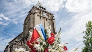 epa05445431 Flowers are displayed at a makeshift memorial in front of the Saint Etienne church where Priest Jacques Hamel was killed on 26 July in a terror related attack, in Saint-Etienne-du-Rouvray, near Rouen, 28 July 2016. The two hostage takers were