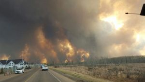 This photo take through a car windshield shows smoke rising from a wildfire rages outside of Fort McMurray, Alberta, Tuesday, May 3, 2016. The entire population of the Canadian oil sands city of Fort McMurray, has been ordered to evacuate as a wildfire