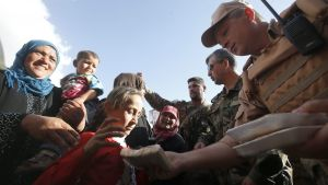 epa05290064 A Russian officer gives humanitarian aid  to residents during a delivery by the Russian army in a village of Kaukab, Hama province, Syria, 04 May 2016. The United States and Russia have agreed to extend the cease-fire in Syria to the city of