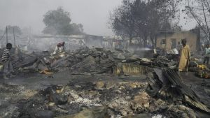 epa03095737 Nigerian boys sift through the remains of the Gamboru market after multiple explosions in Maiduguri, northern Nigeria, 07 February 2012. Three people have died in bomb blasts by the radical Islamist group Boko Haram in northern Nigeria, police