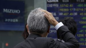 epaselect epa05386882 A pedestrian reacts in front of a monitor displaying the Tokyo stock index in Tokyo, Japan, 24 June 2016. The benchmark Nikkei 225 Stock Average lost 495.95 points, or 3.05 percent, to end the morning session at 15742.40 after