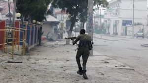 A Somali soldier takes position during an attack on Nasahablod Hotel, in Mogadishu, Somalia, Saturday, a June 25, 2016 . A Somali police officer says a suicide car bomber detonated an explosives-laden vehicle at the gate of a hotel in Mogadishu followed