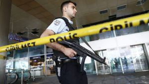 epa05397160 An armed Turkish policeman patrols behind a police line after multiple suicide bomb attacks at Ataturk international airport in Istanbul, Turkey, 29 June 2016. At least 36 people were killed and more than 140 others were wounded in three