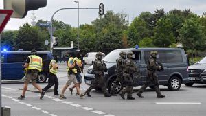 epaselect epa05437039 Special police forces rush to the scene at a shopping centre where a shooting was taking place in Munich, Germany, 22 July 2016. Several people were reported dead by the police and several more injured after a shooting in the Olympia