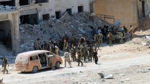 epa05445567 A handout photo released by the official Syrian Arab News Agency (SANA) on 28 July 2016 shows Syrian government soldiers patrolling in al-Layramoun and Bani Zein neighborhoods after recapturing from rebels in the northern province of Aleppo,