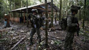Anti-narcotics police officers walk in front of an illegal cocaine lab about to be destroyed in Calamar, Guaviare state, Colombia, Tuesday, Aug. 2, 2016. Police seized cocaine and chemicals at the lab, which according to the commander of the anti