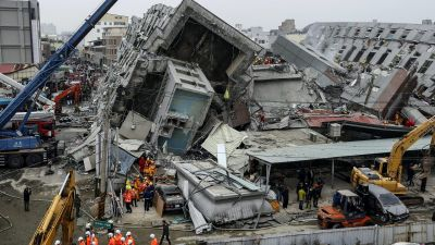 epa05145449 Rescuers search for survivors from a collapsed building following a 6.4 magnitude earthquake that struck the area in Tainan City, Taiwan, 06 February 2016. At least three people, including an infant, were killed and dozens injured when a high