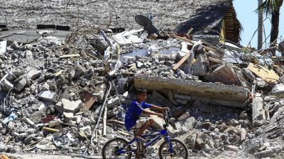 epaselect epa05277536 A boy rides a bicycle in front of debris of a destroyed building in Canoa, Ecuador, 25 April 2016. The death toll from the magnitude 7.8 earthquake that hit Ecuador's north coast on 16 April has risen to 655, according to the