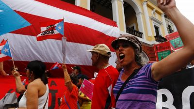 epa05286478 Puerto Ricans march to reject the proposal of a fiscal control board as a measure to solve the fiscal crisis on the island during International Worker's Day in San Juan, Puerto Rico, 01 May 2016. Labour Day, or May Day, is observed all