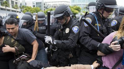 epa05333015 Police officers push protesters opposed to US Republican Party presidential candidate Donald Trump as they try to break up the crowd after Trump's rally at the Convention Center in San Diego, California 27 May 2016. Trump is campaigning