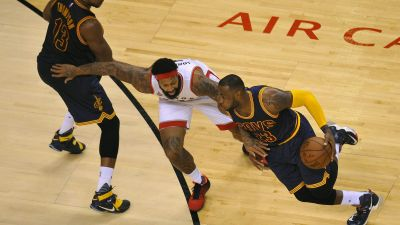 epa05333035 Cleveland Cavaliers center Tristan Thompson of Canada (L) watches as teammate forward LeBron James (R) charges past Toronto Raptors forward James Johnson (C) during the third quarter of game six in the NBA Eastern Conference basketball finals