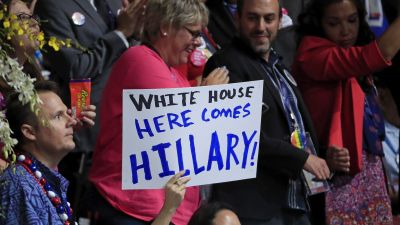 "epa05442446 A supporter of Hillary Clinton holds a sign reading ""White House Here Comes Hillary"" on the second day of the Democratic National Convention at the Wells Fargo Center in Philadelphia, Pennsylvania, USA, 26 July 2016. The four-day"