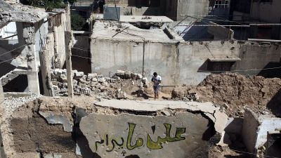 epa05589326 A picture made available on 17 October 2016 showing a man walk next to graffiti painted by Noorthat reads in arabic 'all is right' painted by Syrian graffiti artist Noor, in rebel-held al-Qaboon nieberhood, outskirts of Damascus,