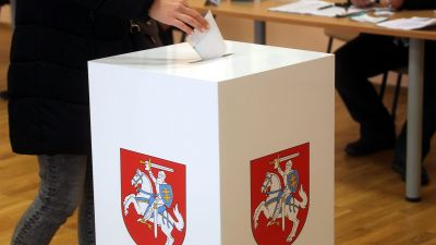 epa05599568 A voter drops a ballot during the second round of Lithuanian parliamentary election in Birzai, Lithuania, 23 October 2016. The Lithuanian parliament (Seimas) consists of 141 members including 71 in single-seat constituencies and 70 by party