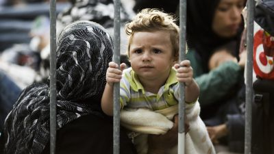 A child sits with other refugees behind a fence  between Croatia and Slovenia at the border station of Obretzje, Slovenia, Saturday, Sept. 19, 2015.  Slovenian police block the crossing for the refugees into the country. (AP Photo/Markus Schreiber)