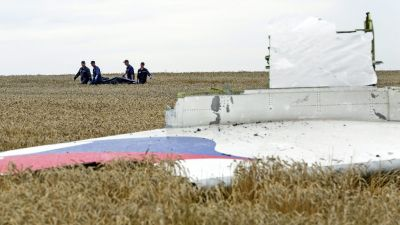 epa04975641 (FILE) People carry a stretcher with a bodybag past the debris of a Boeing 777 Malaysia Airlines flight MH17 airplane, which crashed during flying over the eastern Ukraine region, at the crash site near Donetsk, Ukraine, 19 July 2014. The