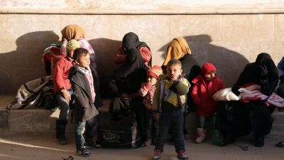In this photo provided by Turkey's Islamic aid group of IHH, Syrians fleeing the conflicts in Azaz region, wait at the Bab al-Salam border gate, Syria, Friday, Feb. 5, 2016. Turkish officials say thousands of Syrians have massed on the Syrian side of