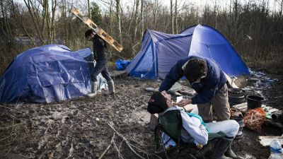epa05104948 Iraqi Kurdish migrants Saad shaves his friend Mani next to their tent in the makeshift migrant camp in Grande-Synthe near Dunkirk, or Dunkerque, France, 16 January 2016. Despite most of the attention is on the so-called 'Jungle' in