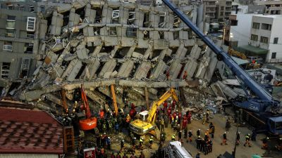 epa05147395 Rescuers search for survivors from a collapsed building following a 6.4 magnitude earthquake struck on 06 February in Tainan City, southern Taiwan, 07 February 2016. Dozens were killed and hundreds injured when a 6.4-magnitude earthquake