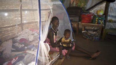 In this photo taken Tuesday, Jan. 19, 2016, Nyajok Koat sits with her one year-old son Thach Kuony in her makeshift home covered with plastic sheets, in the United Nations camp for displaced people in the capital Juba, South Sudan.When a delegation of