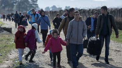 epa05160351 Refugees walks to the transit and registration camp after they cross the border between Greece and Macedonia  near city of Gevegelia, The Former Yugoslav Republic of Macedonia on 14 February 2016. Thousand of refugees continue to pass through